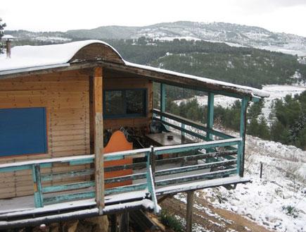 בקתת עץ על רקע הרים מושלגים בבקתה בקדיתא