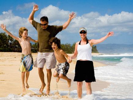טיולי משפחות: משפחה מאושרת על חוף הים (צילום: iStock)