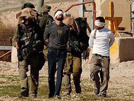 חיילי צהל צועדים לצד עצורים פלסטינים (צילום: רויטרס)