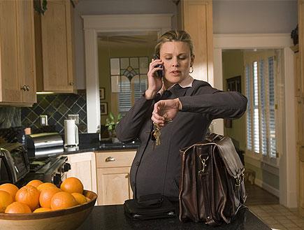 אישה מחוייטת בהריון מחזיקה מפתחות ומסתכלת בשעון (צילום: jupiter images)