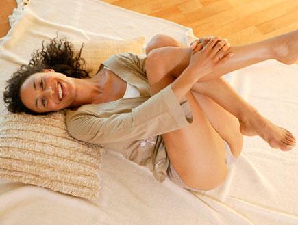 בחורה שוכבת במיטה מחבקת את רגליה ומחייכת (צילום: jupiter images)