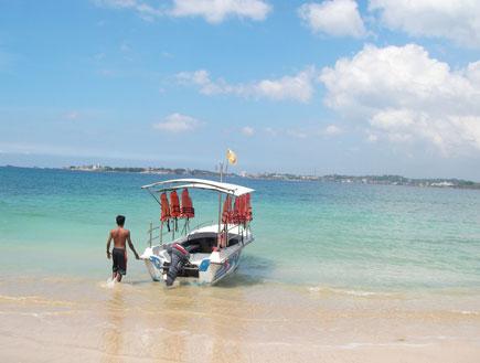 איש עם סירת מנוע קטנה בחוף היקדווה בסרי לנקה