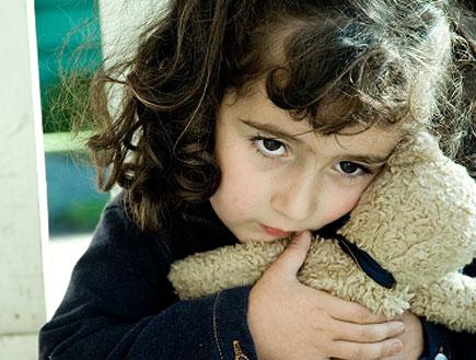 ילדה מפוחדת בשחור מחבקת דובי ליד גדר (צילום: istockphoto)