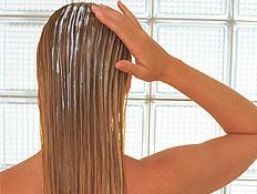 קשרים בשער- בחורה במגבת מורחת מרכך על שער רטוב (צילום: jupiter images)