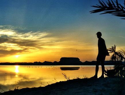 דמות אדם שחור מול אגם שהשקיעה משתקפת בו (צילום: אור גץ, SXC1)