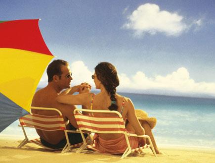 גבר ואישה יושבים בים עם שמשייה