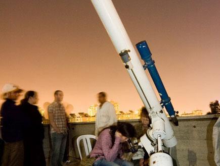 בחורה מסתכלת בטלסקופ במצפה הכוכבים בגבעתיים (צילום: איציק מרום)