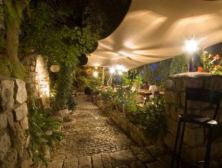 כסא בר בפתח שביל אבן מוקף צמחיה בראש פינה בלילה (צילום: איציק מרום)