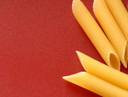 פסטה פנה לא מבושלת על רקע משטח אדום (צילום: EHStock, Istock)