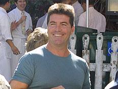 סיימון קאוול מחייך בטישירט תכלת לפני גדר צבועה לבן (צילום: רויטרס)