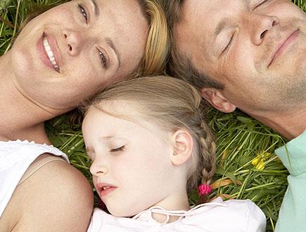 הורים לילדים - אבא אמא וילדה שוכבים על הדשא (צילום: jupiter images)