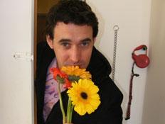 בחור מחזיק פרחים בפתח דלת (צילום: איתי בוטבגה)