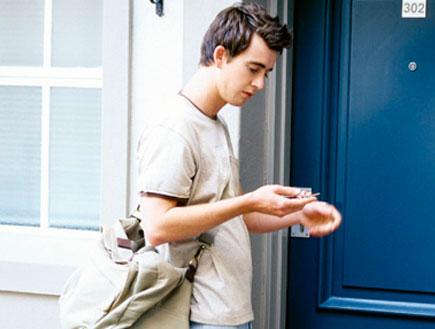 צעיר מחפש מפתח להיכנס לבית עם דלת כחולה (צילום: jupiter images)