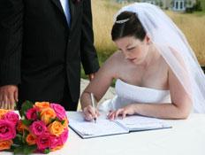 כלה כותבת ביומן, חתן עומד לצידה,זר פרחים על השולחן