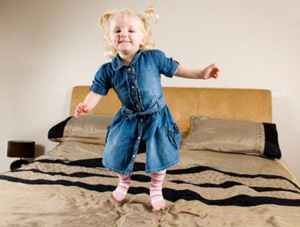 ילדה קופצת על מיטת הורים