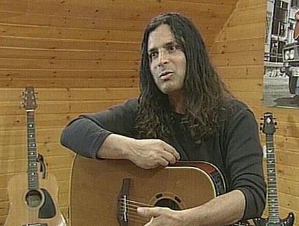 מיכה ביטון עם גיטרה ביד ושתיי גיטרות מאחוריו (תמונת AVI: חדשות)