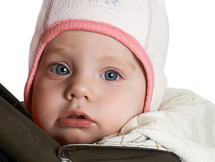 תינוק עם עיניים כחולות בכובע ורוד ולבן (צילום: istockphoto)