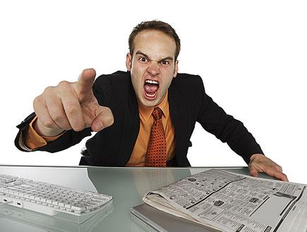 בחור בחליפה ליד שולחן מרים אצבע וצועק בכעס (צילום: jupiter images)