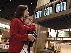 אמא מחזיקה בנה ומסתכלת על לוח טיסות בשדה תעופה (צילום: jupiter images)
