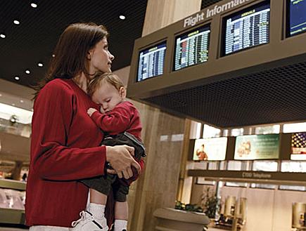 אמא מחזיקה בנה ומסתכלת על לוח טיסות בשדה תעופה