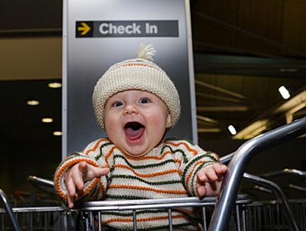 תינוק עם פסים צוחק בעגלה בצ'ק אין