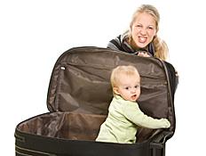 תינוק במזוודה פתוחה ומאחוריה בחורה עושה פרצוף (צילום: istockphoto)