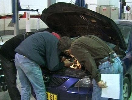 טכנאי רכב מביט במנוע של רכב במוסך