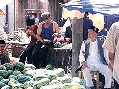 סינים אוכלים אבטיחים בשוק בטורפאן שבסין (צילום: דוד אפיק)