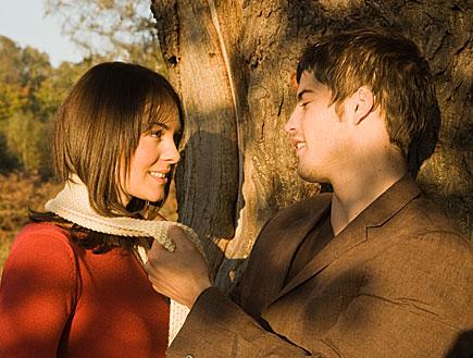 בחור עומד ליד עץ ומושך לבחורה בצעיף (צילום: jupiter images)