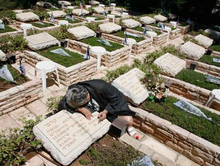 אישה מבוגרת בוכה על קבר בבית קברות