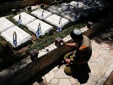 חייל מדליק נר נשמה בבית קברות
