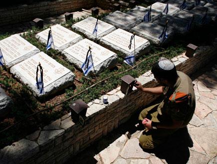 חייל מדליק נר נשמה בבית קברות (תמונת AVI: עדי רם, חדשות)