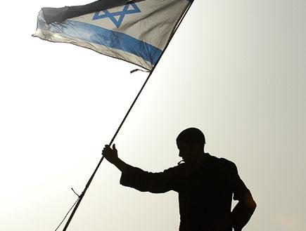 אדם עם דגל ישראל ביד (תמונת AVI: עדי רם, חדשות)