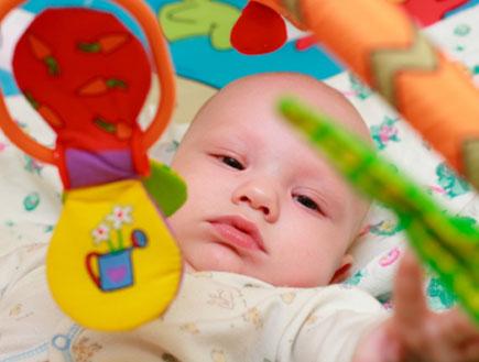 תינוק שוכב ומשחק עם מוביילים צבעוניים (צילום: istockphoto)