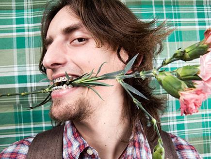 חנון עם פלטה מחזיק פרחים בשיניים (צילום: Alija, Istock)