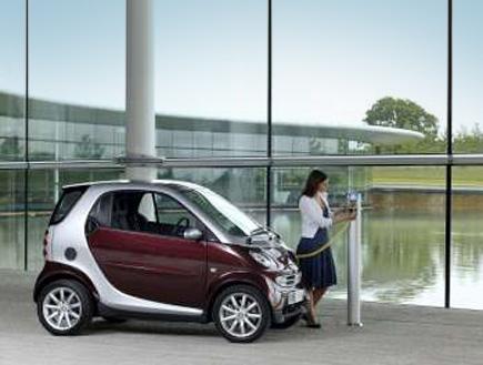 בחורה מטעינה מכונית סמארט בשקע חשמל (צילום: עדי רם)