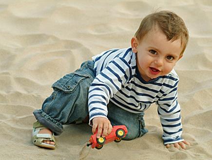 ילד בחולצה מפוספסת משחק במכונית צעצוע על החול (צילום: istockphoto)