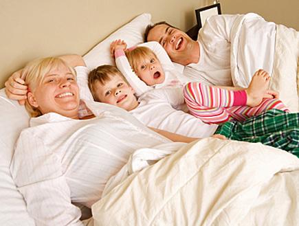 הורים ושני ילדיהם במיטה אחת (צילום: Leigh Schindler, Istock)