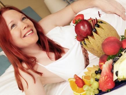 בחורה ג'ינג'ית בהריון שוכבת ליד מגש פירות (צילום: hidesy, Istock)