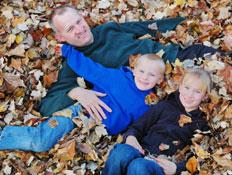 אב ושני ילדיו שוכבים בתוך עלי שלכת