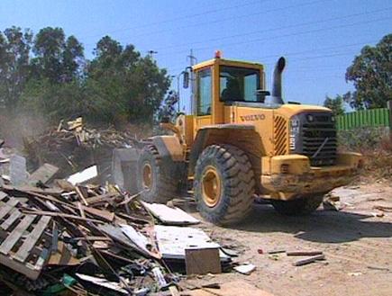 טרקטור באתר בנייה עם עצים וקרשים (תמונת AVI: עדי רם, חדשות)