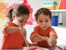 שני ילדים לבושים כתום מציירים (צילום: Weekend Images Inc., Istock)