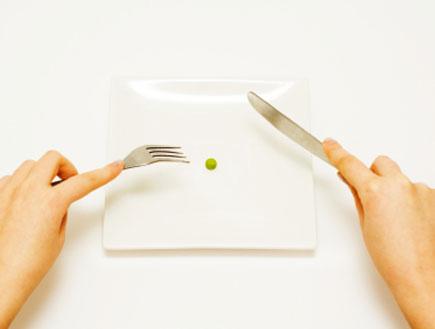אישה אוכלת גרגר אפונה בודד עם סכין ומזלג (צילום: amoceptum, Istock)