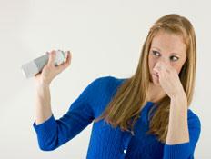 אישה בכחול משפריצה מטהר אוויר וסותמת את האף (צילום: Steve Cady, Istock)