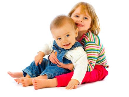 ילדה בחולצת פסים מחבקת תינוק באוברול ג'ינס (צילום: Justin Allfree, Istock)