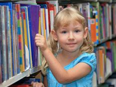 ילדה עם צמות בלונדיניות בוחרת ספר בספרייה (צילום: pamspix, Istock)