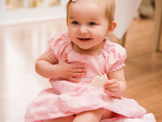 תינוקת בשמלה ורודה יושבת על ריצפת עץ (צילום: snapphoto, Istock)