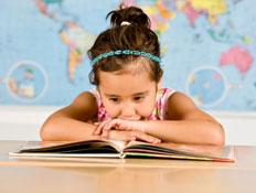 ילדה עם קשת תכולה בשיערה נשענת קדימה וקוראת בספר