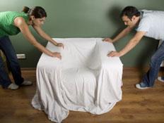 זוג ממקם ספה עטופה בסדין לבן (צילום: istockphoto)