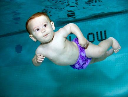 תינוק עם בגד ים סגול צולל לבדו בבריכת שחייה (צילום: istockphoto)